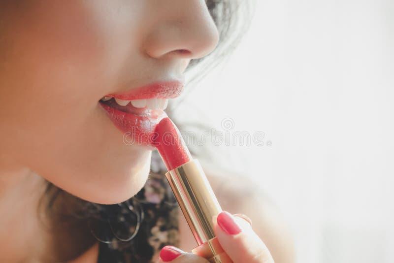 Chiuda sulla bella giovane donna di lusso che si applica la fodera del labbro alle labbra rosse nude Chiuda sul colpo e componga immagine stock libera da diritti