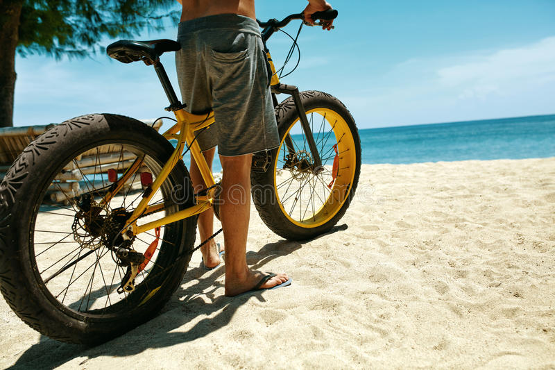 Chiuda sulla bicicletta della sabbia di guida dell'uomo sulla spiaggia Sport di estate fotografie stock