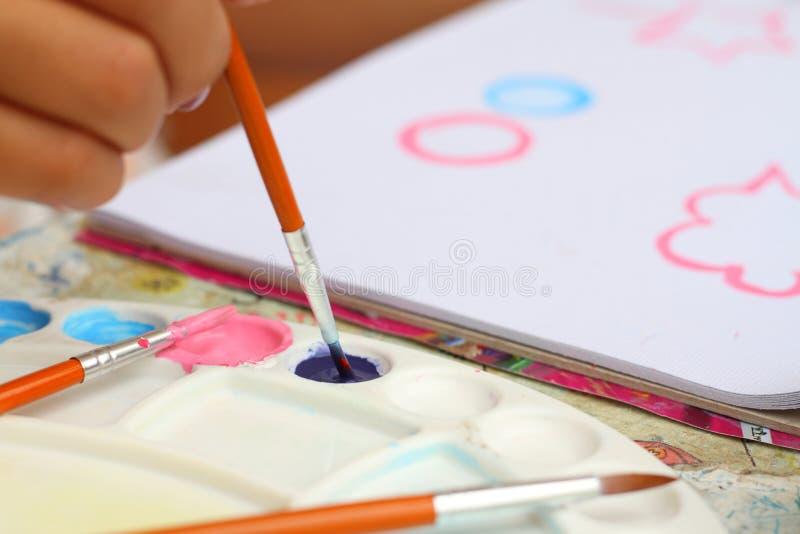 Chiuda sulla carta dell'acquerello della pittura del bambino di arte della mano per istruzione immagine stock libera da diritti