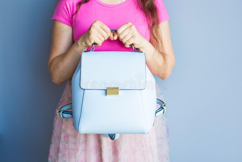 Chiuda sulla donna alla moda in gonna rosa con la borsa blu Concetto di modo fotografia stock