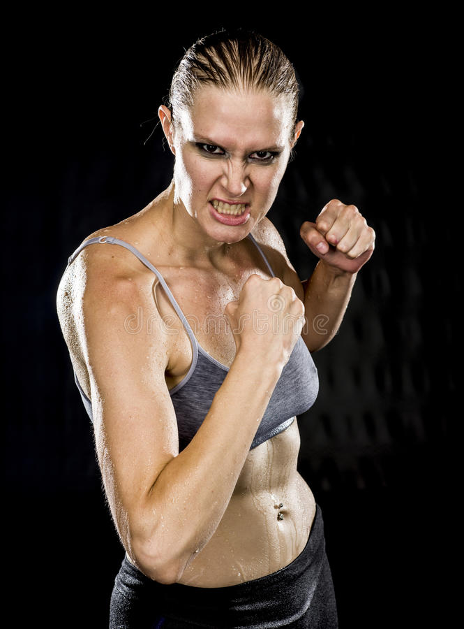 Chiuda sulla donna atletica aggressiva nella posa di combattimento fotografia stock