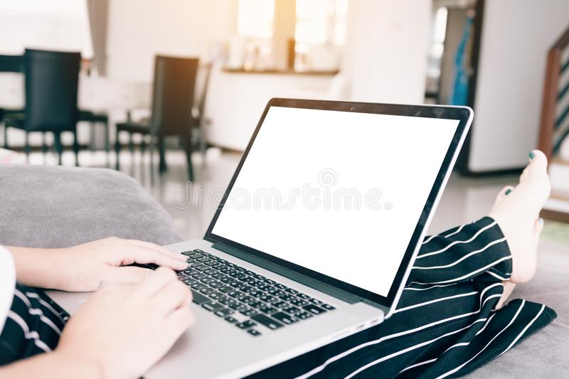 Chiuda sulla donna che per mezzo del computer portatile con lo schermo in bianco fotografia stock libera da diritti
