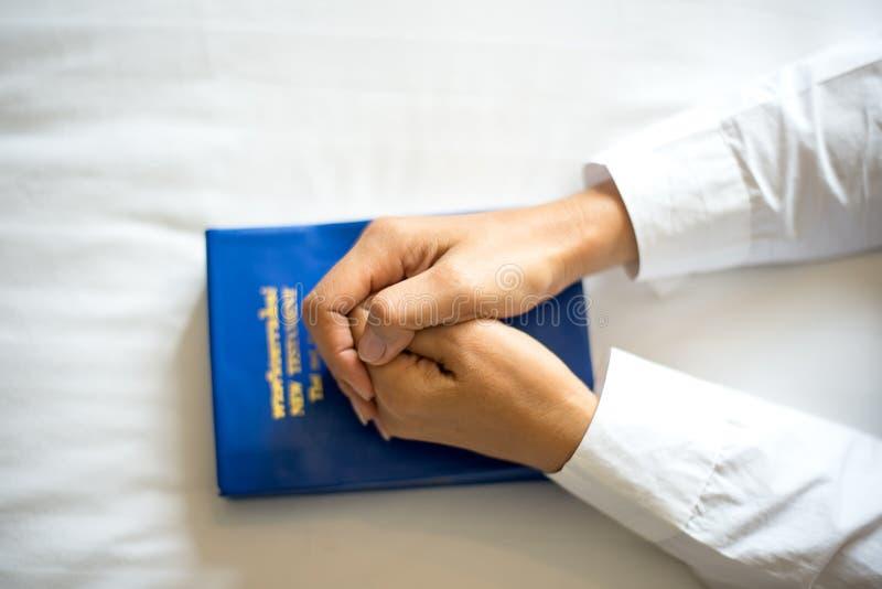 Chiuda sulla donna che prega, mani della mano afferrate insieme sulla sua bibbia immagini stock