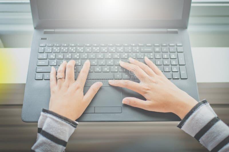 Chiuda sulla donna delle mani che lavora facendo uso del computer portatile immagine stock libera da diritti