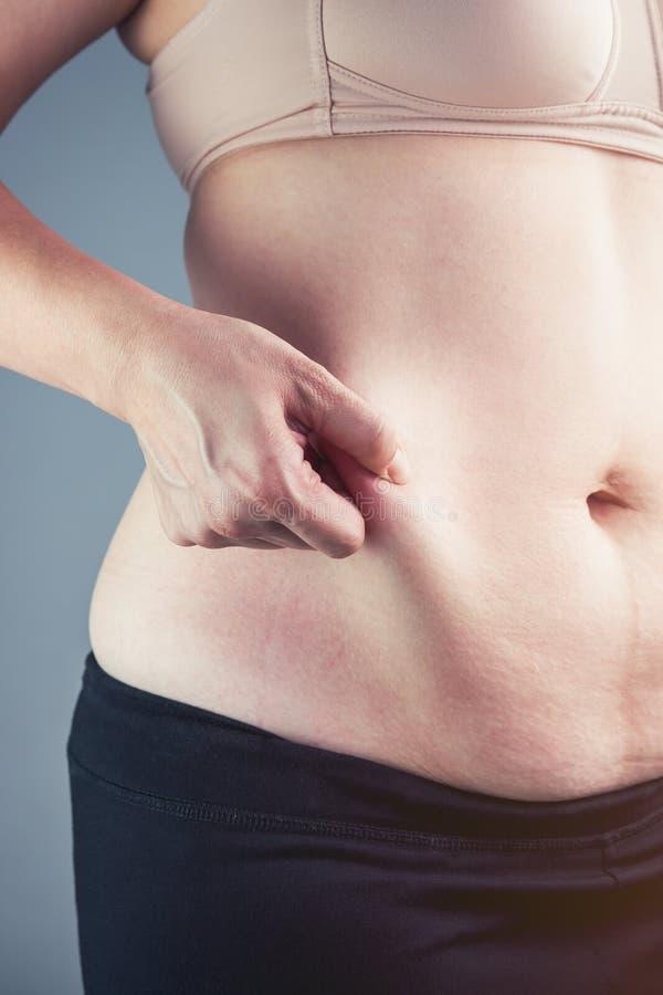 Chiuda sulla femmina che controlla il grasso sull'addome, fondo grigio fotografia stock