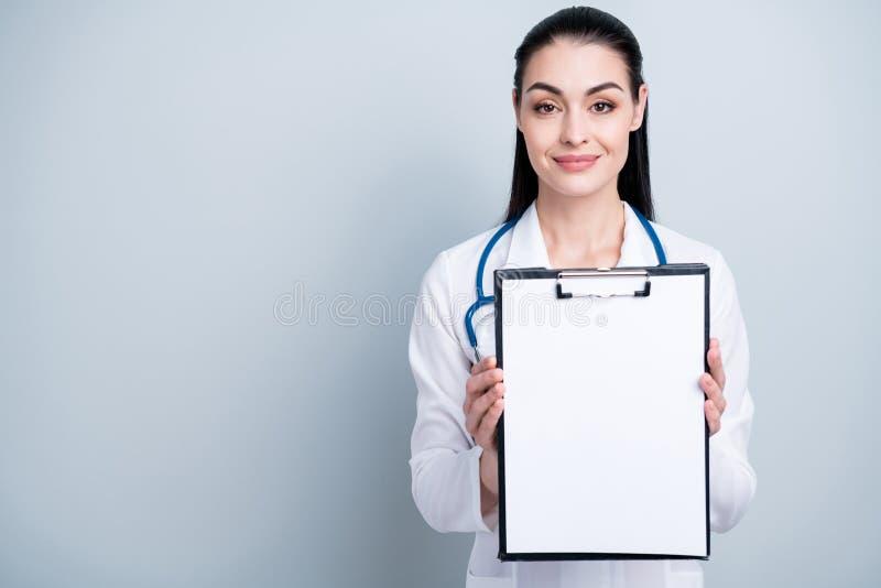 Chiuda sulla foto bella lei la sua usura paziente di firma di assicurazione di anamnesi della lista del posto di rappresentazione fotografie stock libere da diritti