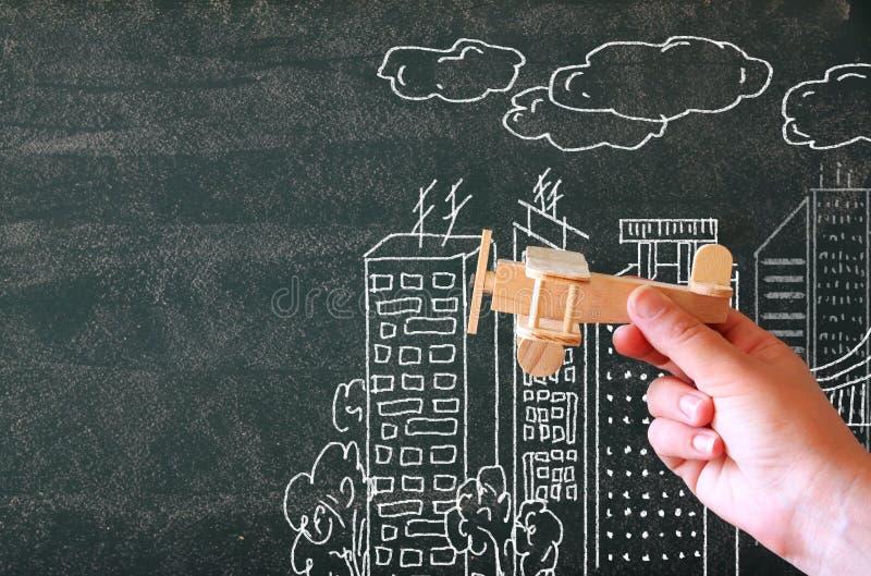 Chiuda sulla foto della mano della donna che tiene l'aeroplano di legno del giocattolo contro la lavagna con l'illustrazione dell fotografie stock libere da diritti