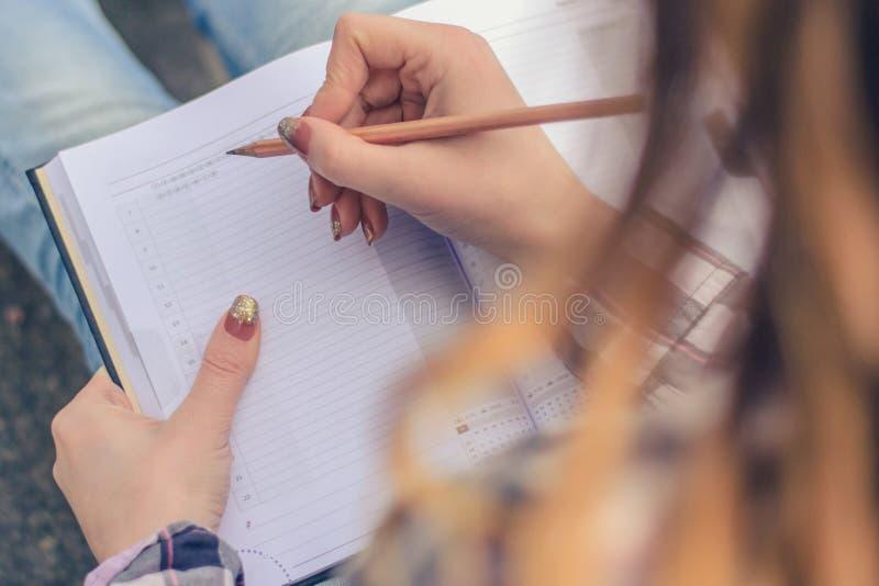 Chiuda sulla foto delle mani del ` s della ragazza che scrivono la composizione in suo diario fotografia stock
