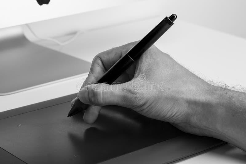 Chiuda sulla foto di una mano del ` s dell'uomo che tiene una penna digitale fotografie stock libere da diritti