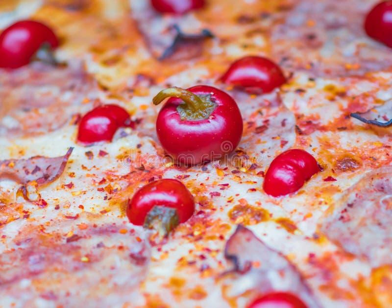 Chiuda sulla foto isolata di una pizza del pomodoro, del bacon e dei peperoncini rossi immagini stock libere da diritti