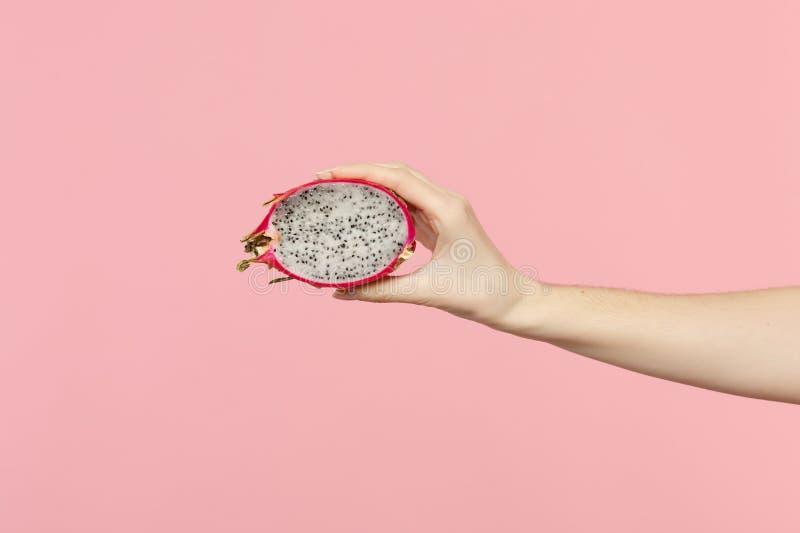 Chiuda sulla foto potata del pitahaya fresco disponibile di metà della tenuta femminile, frutta del drago isolata sul fondo paste fotografia stock libera da diritti