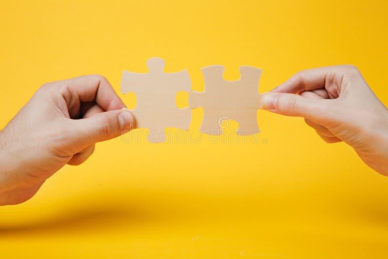 Chiuda sulla foto potata delle mani che tengono che prova a collegare i pezzi di legno del puzzle delle coppie su giallo luminoso immagine stock libera da diritti