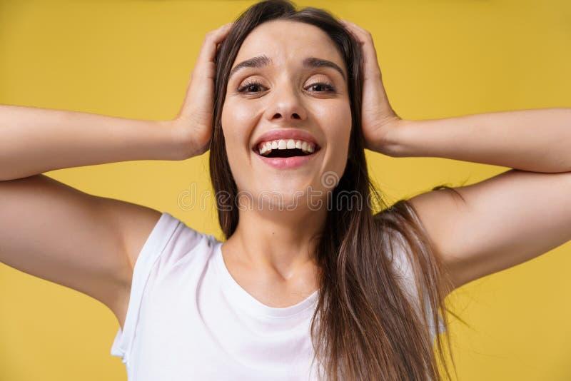 Chiuda sulla giovane bella ragazza attraente dello studente del ritratto che colpisce con qualcosa Priorità bassa gialla luminosa immagini stock