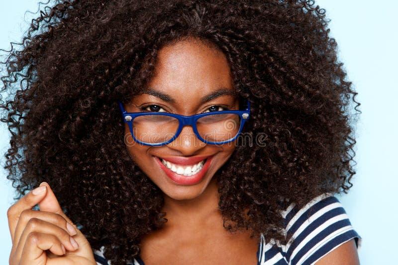 Chiuda sulla giovane donna afroamericana con i vetri d'uso dei capelli ricci immagini stock libere da diritti
