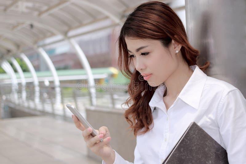 Chiuda sulla giovane donna asiatica attraente di affari che esamina lo Smart Phone mobile in sue mani l'ufficio esterno con il ba immagini stock