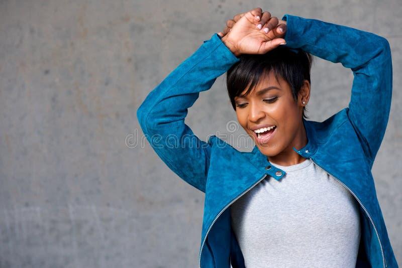 Chiuda sulla giovane donna di colore d'avanguardia che sorride contro la parete grigia fotografie stock
