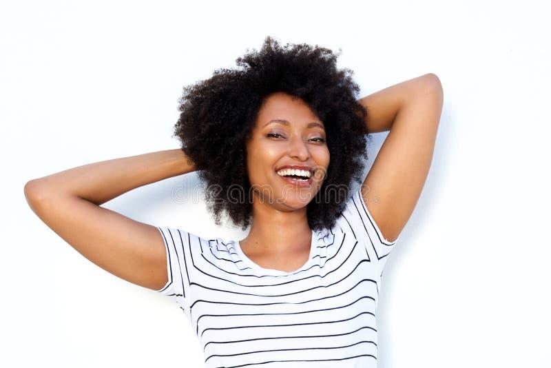 Chiuda sulla giovane donna di colore felice con le mani dietro capelli e sul sorridere sul fondo bianco immagine stock