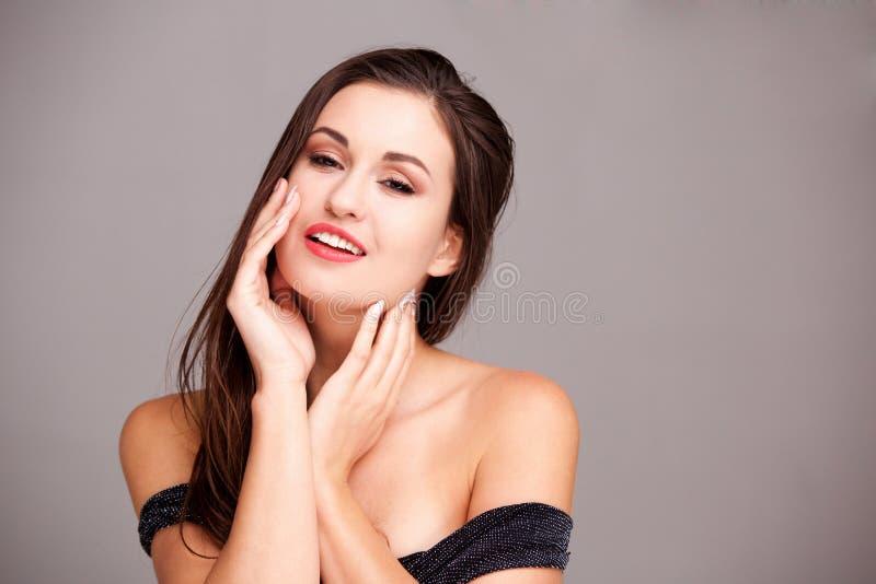 Chiuda sulla giovane donna elegante con le mani sul fronte contro la parete grigia fotografia stock