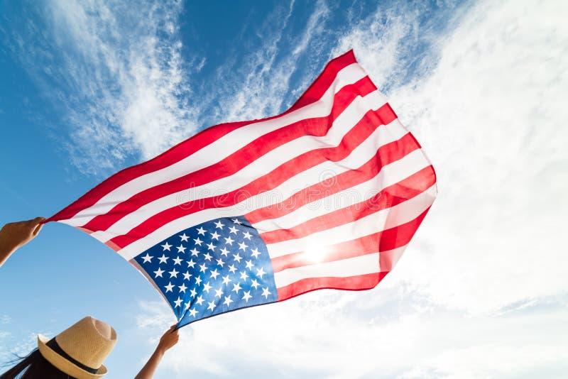 Chiuda sulla giovane donna felice che tiene la bandiera degli Stati Uniti d'America immagini stock