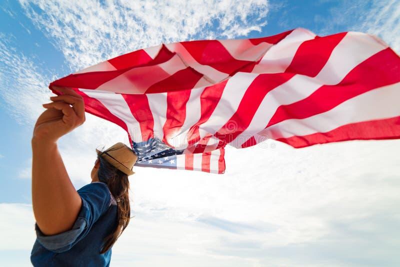 Chiuda sulla giovane donna felice che tiene la bandiera degli Stati Uniti d'America immagine stock