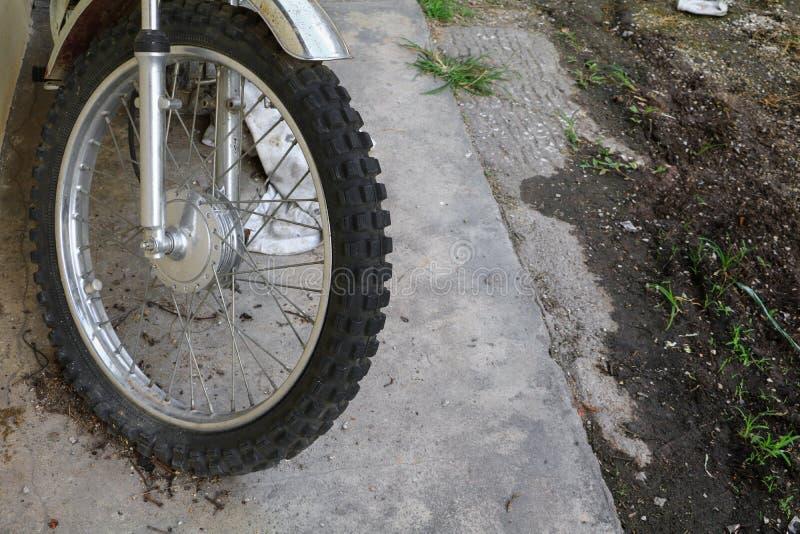 Chiuda sulla gomma piana della ruota del motociclo vecchio e incrinato fotografia stock