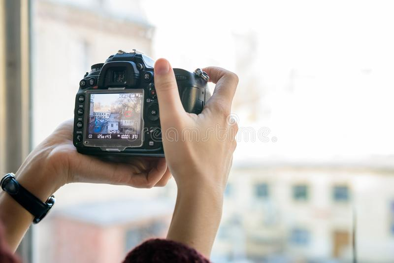 Chiuda sulla macchina fotografica femminile del professionista della tenuta delle mani fotografia stock libera da diritti