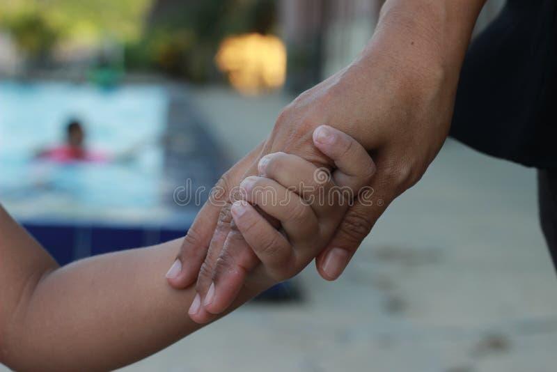 Chiuda sulla madre che tiene la sua mano del ` s dei bambini alla piscina, il tono naturale immagini stock libere da diritti