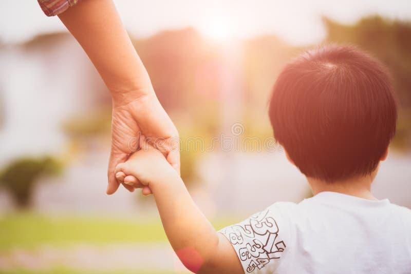 Chiuda sulla madre che tiene una mano del ` s del bambino fotografia stock