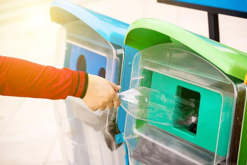 Chiuda sulla mano del fuoco selettivo che getta la bottiglia di plastica vuota nei rifiuti La mano della donna che mette la plast immagini stock libere da diritti