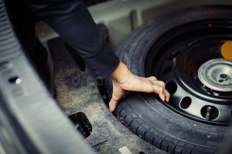 Chiuda sulla mano del meccanico che prende la ruota di scorta allo stivale in automobile immagini stock