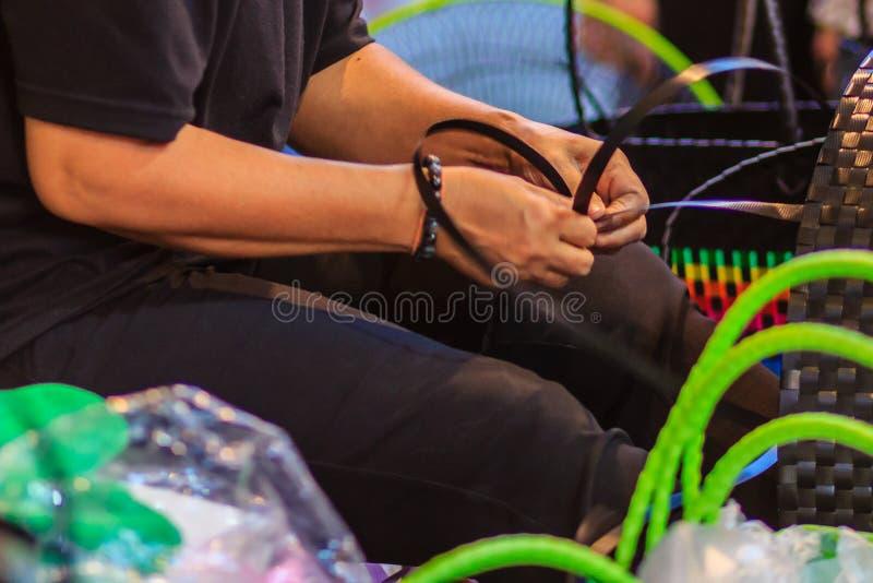 Chiuda sulla mano del tessitore durante il canestro di tessitura fatto da plastica immagine stock