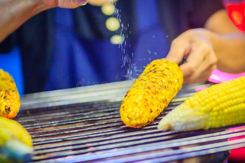 Chiuda sulla mano del venditore di alimento della via mentre grigliano per lo swe misto fotografia stock libera da diritti