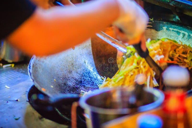 Chiuda sulla mano del venditore durante la cottura per Padthai, l'originale immagini stock libere da diritti