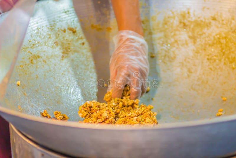 Chiuda sulla mano del venditore tailandese mentre cucinano Krayasat dolce, un dessert tailandese per gli eventi religiosi buddist fotografia stock libera da diritti