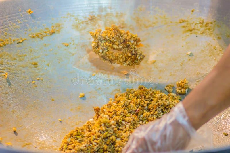 Chiuda sulla mano del venditore tailandese mentre cucinano Krayasat dolce, un dessert tailandese per gli eventi religiosi buddist immagine stock libera da diritti