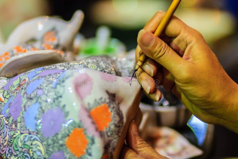 Chiuda sulla mano dell'artista tailandese della donna durante la verniciatura del masterpie fotografia stock