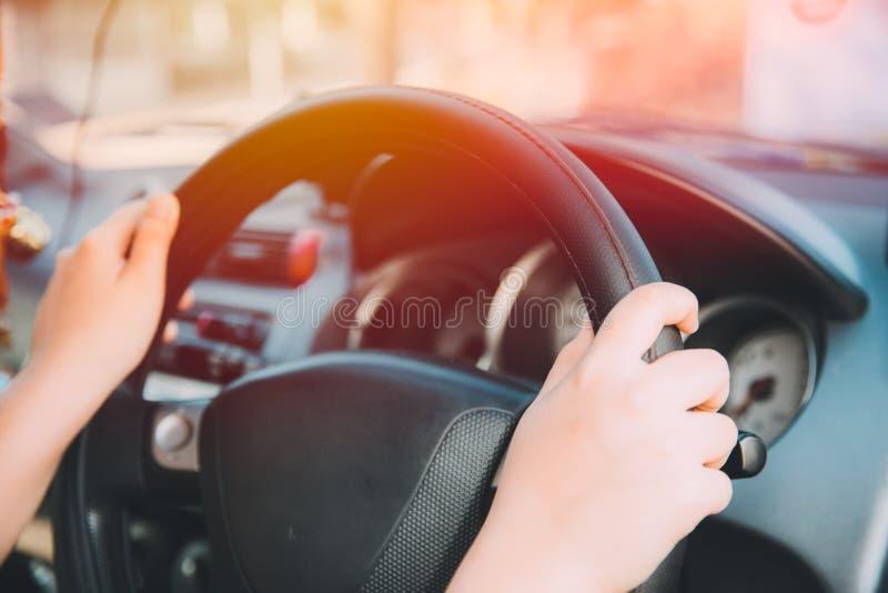 Chiuda sulla mano delle donne che conduce l'automobile della città fotografia stock