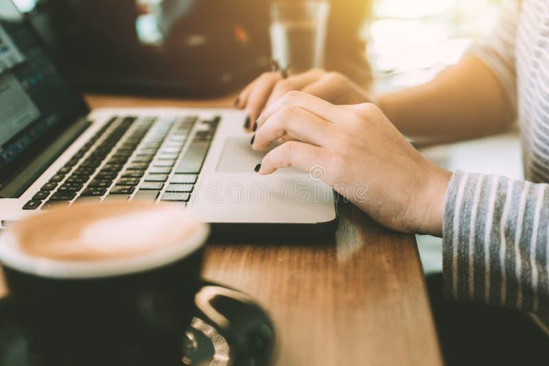 Chiuda sulla mano delle donne dei pantaloni a vita bassa facendo uso del touchpad del computer portatile immagine stock