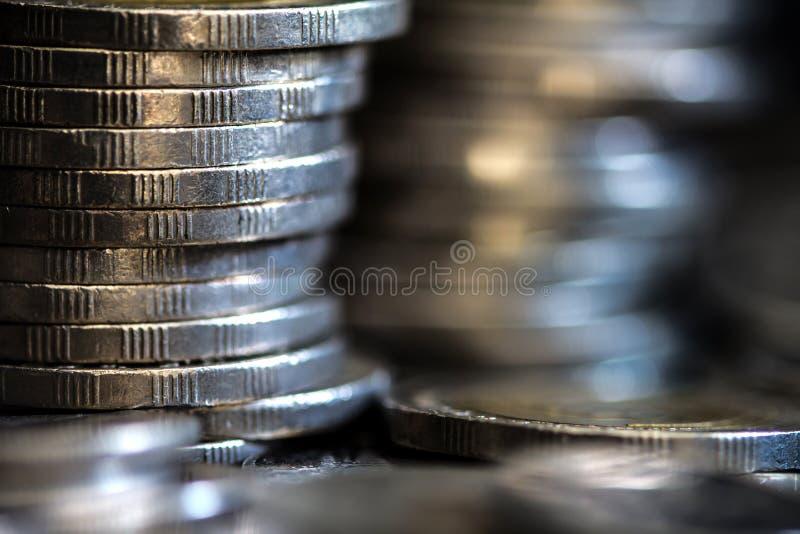 Chiuda sulla moneta d'argento dei soldi che impila sul fondo scuro fotografia stock
