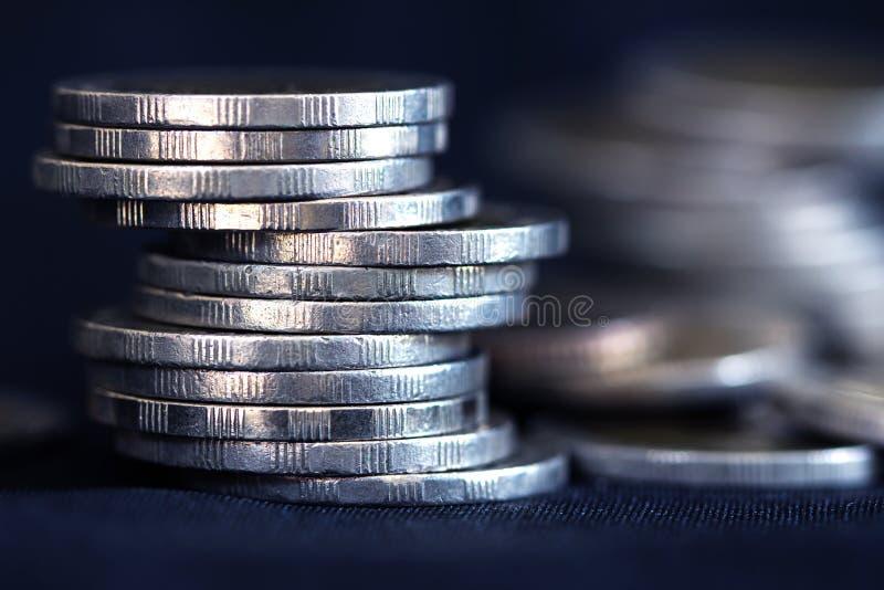 Chiuda sulla moneta d'argento dei soldi che impila sul fondo scuro fotografie stock