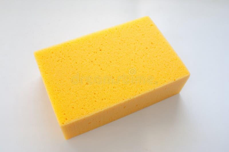 Chiuda sulla nuova spugna gialla su fondo bianco fotografie stock