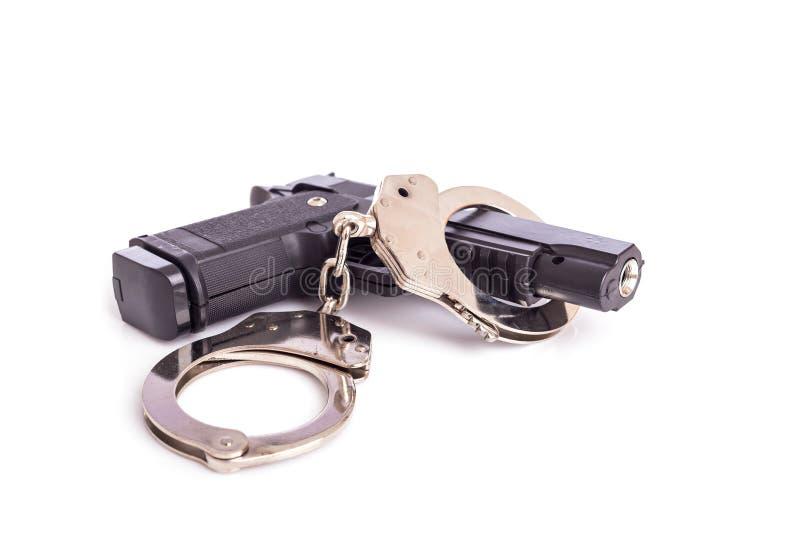 Chiuda sulla pistola e sulle manette isolate su bianco fotografie stock libere da diritti