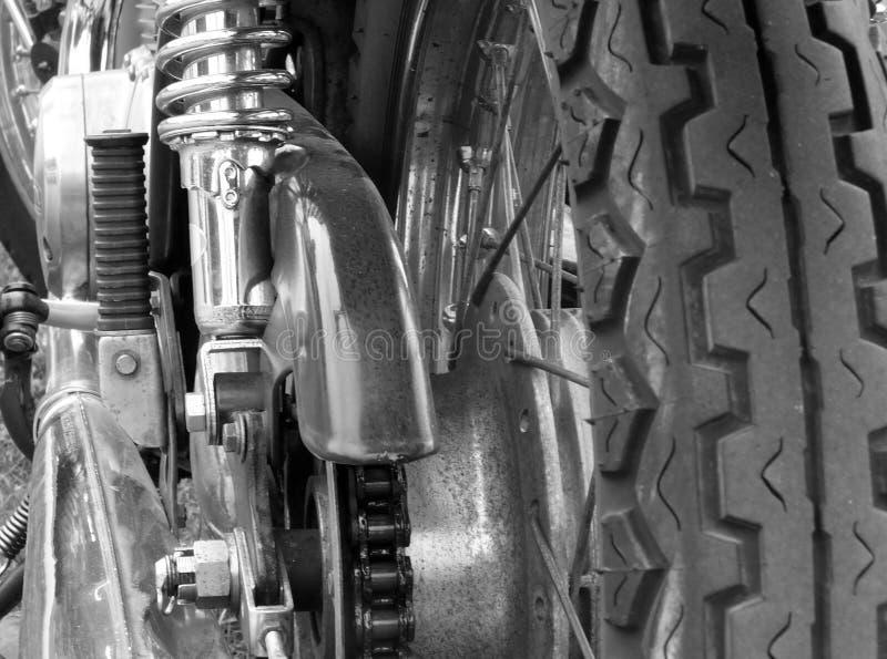 Chiuda sulla retrovisione di un motociclo d'annata con la catena di azionamento dei raggi della ruota dei battistrada e le molle  fotografia stock