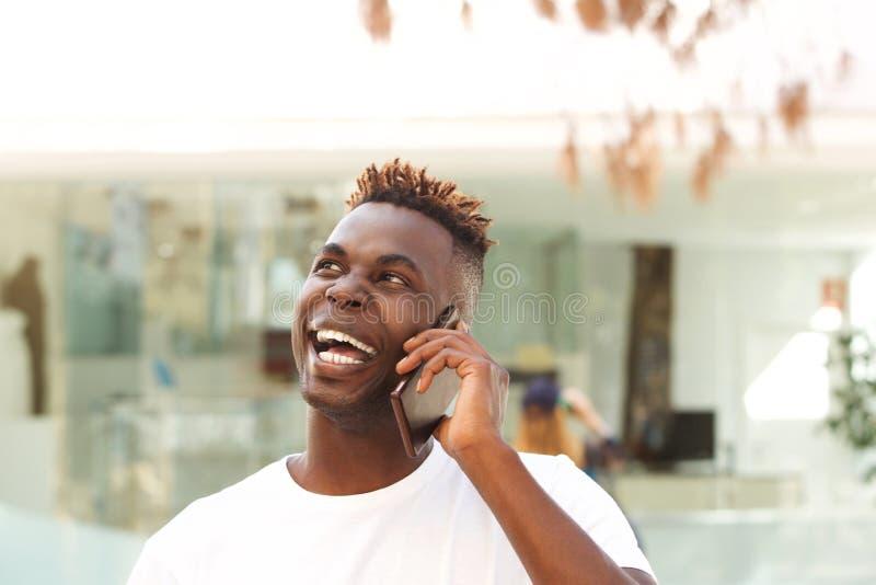Chiuda sulla risata del giovane africano che parla sul telefono cellulare e sul distogliere lo sguardo immagine stock libera da diritti