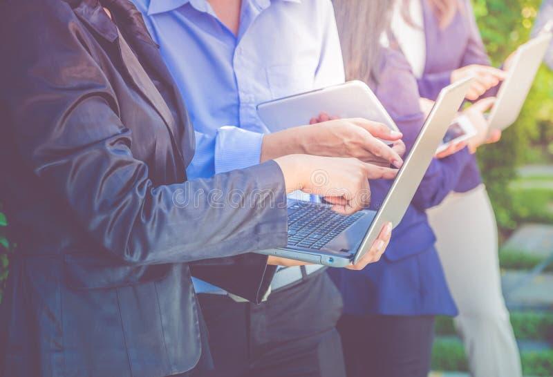 Chiuda sulla riunione del gruppo del gruppo di affari e computer portatile e digita usando fotografia stock