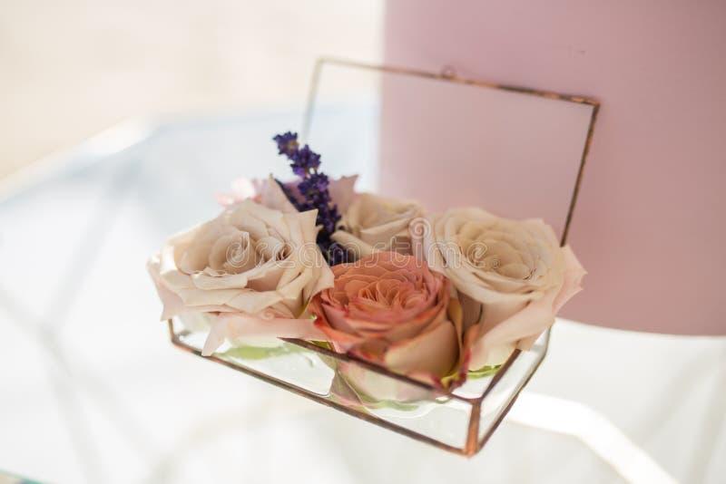 Chiuda sulla scatola di vetro per le fedi nuziali decorate con i fiori e il banch rosa freschi di lavanda Decorazione di evento c immagini stock