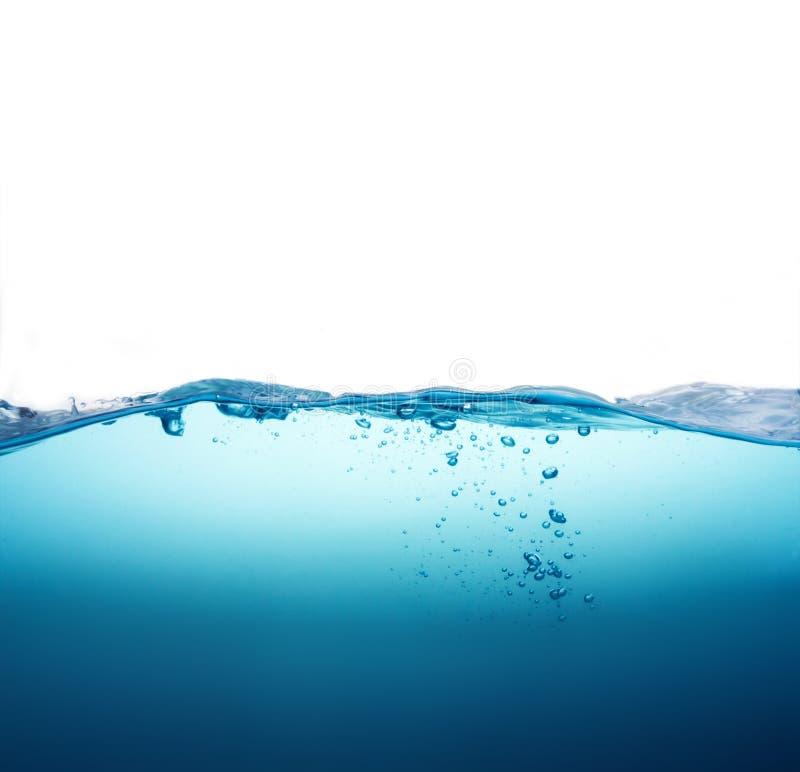 Chiuda sulla spruzzata dell'acqua blu con le bolle su fondo bianco fotografia stock