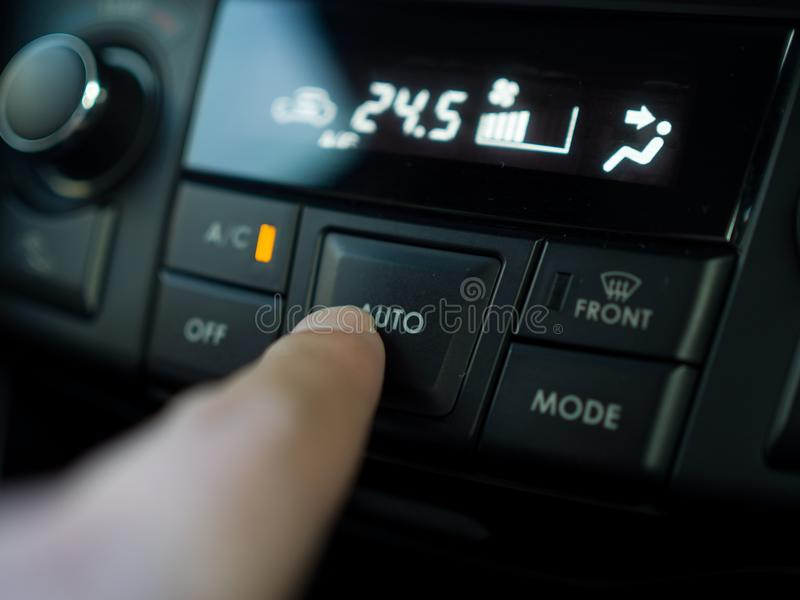 Chiuda sulla stampa del dito il bottone per accendere il termine dell'aria in automobile fotografia stock