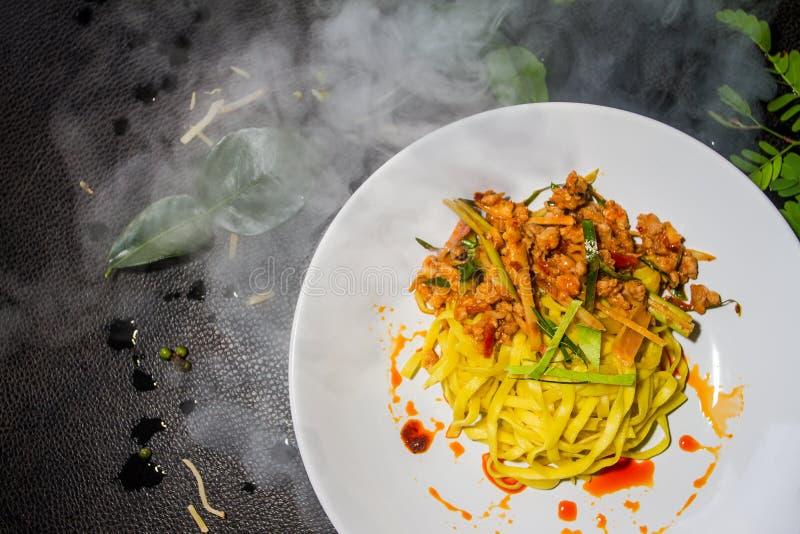 Chiuda sulla tagliatella gialla fritta yum di Tom, piatti bianchi sistemati su un fondo nero Alimento tailandese tradizionale immagine stock