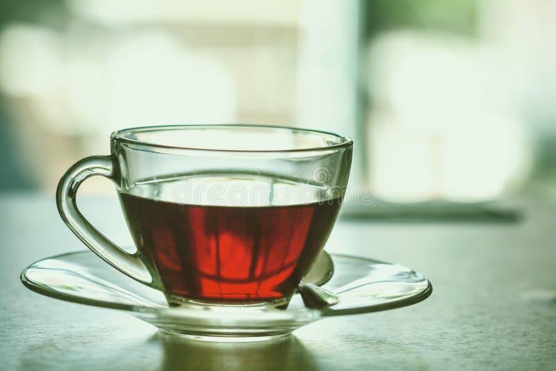 Chiuda sulla tazza di tè nero calda sulla tavola di legno in ro vivente immagine stock